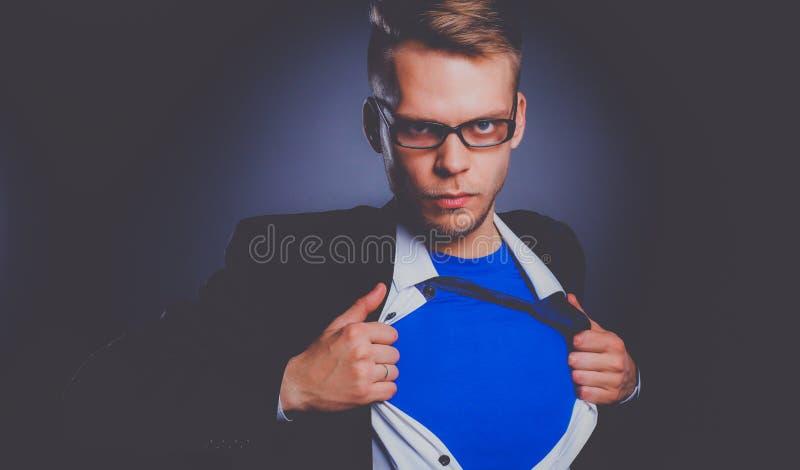Homem de negócios novo que actua como um super-herói e que rasga sua camisa, isolada no fundo cinzento fotografia de stock
