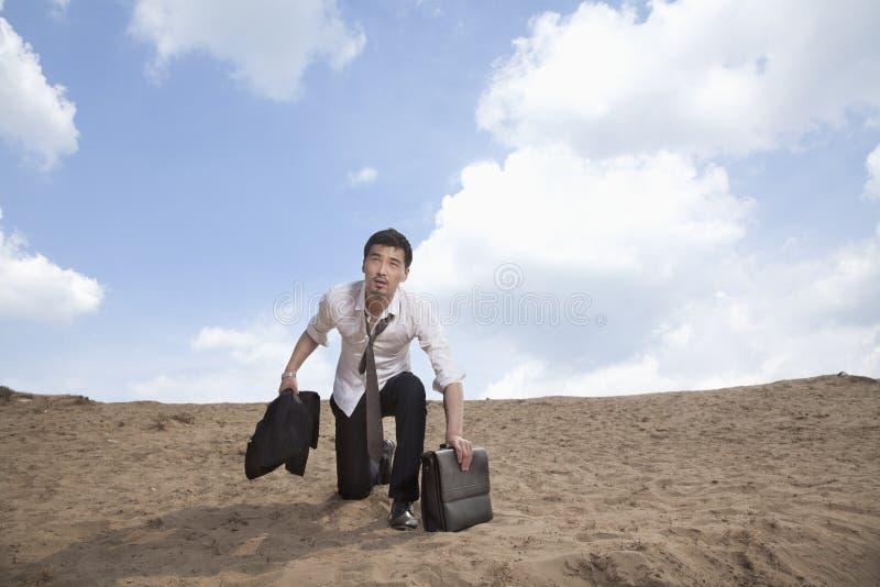 Homem de negócios novo que ajoelha-se no deserto e que guardara uma pasta, esgotada fotografia de stock