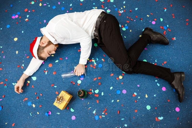 Homem de negócios novo que comemora o Natal no escritório que dorme no assoalho fotografia de stock