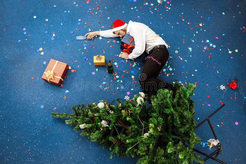 Homem de negócios novo que comemora o Natal no escritório que dorme no assoalho imagem de stock