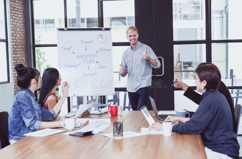 Homem de negócios novo que dá uma apresentação no flipchart a seu equipe do negócio ou grupo de colegas de trabalho, trabalhos de fotos de stock royalty free
