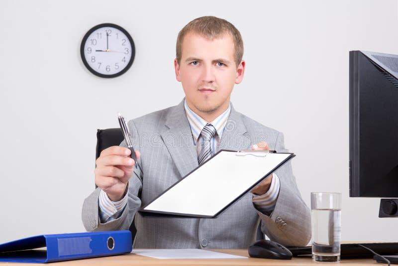 Homem de negócios novo que dá uma pena para assinar um contrato fotografia de stock