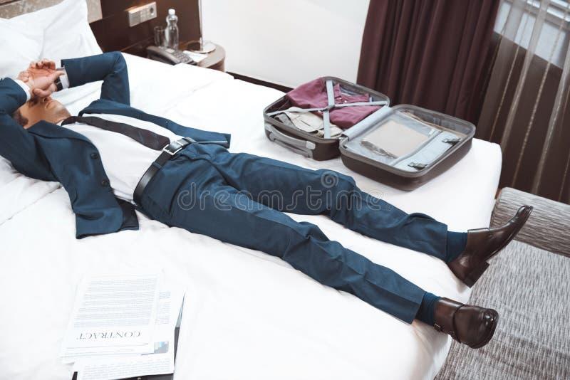 Homem de negócios novo que encontra-se na cama na sala de hotel com coberta das mãos fotos de stock royalty free