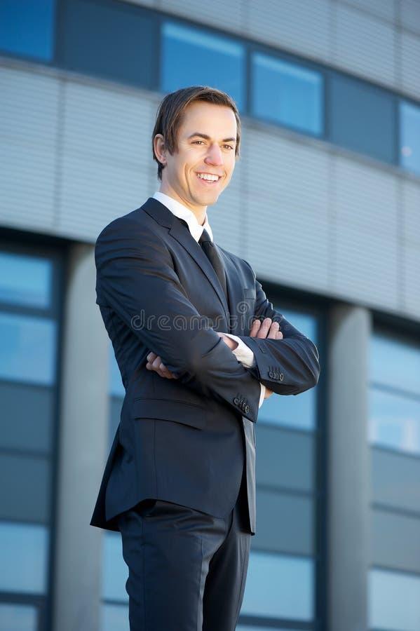 Homem de negócios novo que está fora de sorriso imagens de stock