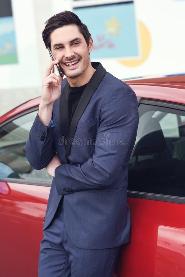 Homem de negócios novo que fala com seu telefone celular perto de um carro fotos de stock royalty free