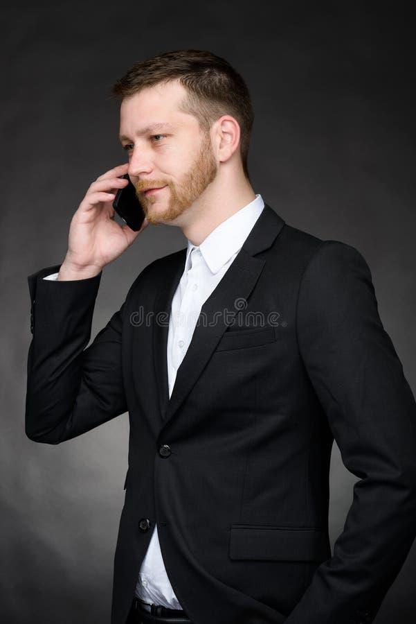 Homem de negócios novo que fala no telefone celular fotografia de stock