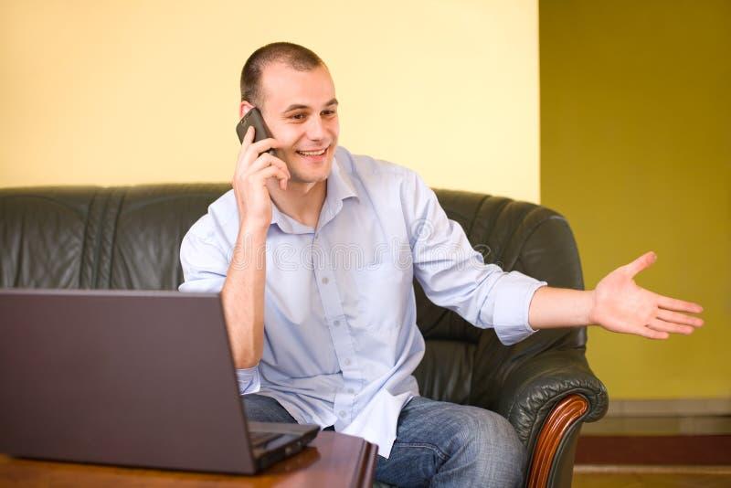 Homem de negócios novo que fala no telemóvel. imagem de stock royalty free