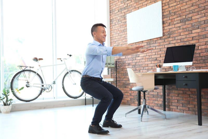 Homem de negócios novo que faz exercícios no escritório foto de stock royalty free