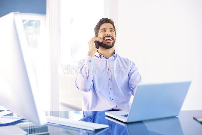 Homem de negócios novo que faz uma chamada ao trabalhar no portátil imagem de stock