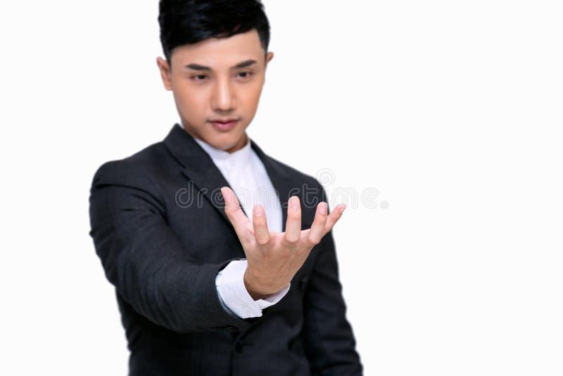 Homem de negócios novo que guarda alguma coisa em sua mão; Estar no fundo branco foto de stock