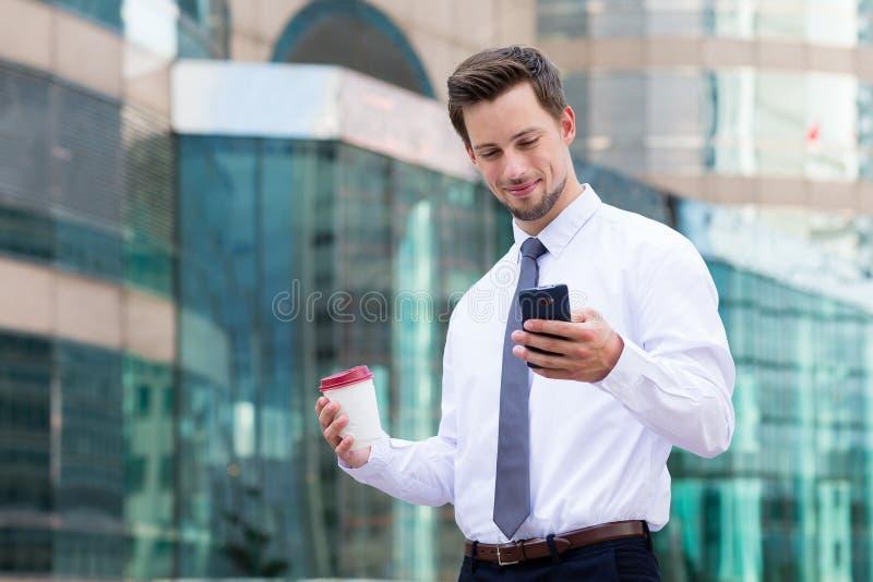 Homem de negócios novo que guarda com telefone celular e café imagens de stock royalty free