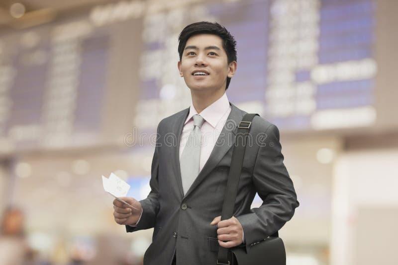 Homem de negócios novo que guarda o bilhete no aeroporto, Pequim, China foto de stock