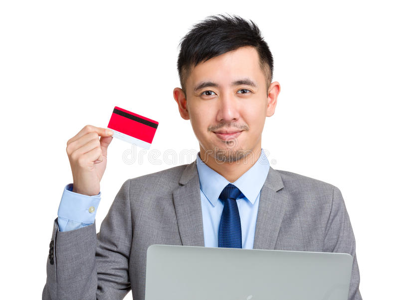Homem de negócios novo que guarda o cartão e o computador de crédito imagens de stock