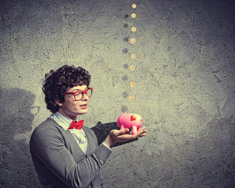 Homem De Negócios Novo Que Guarda O Moneybox Fotos de Stock