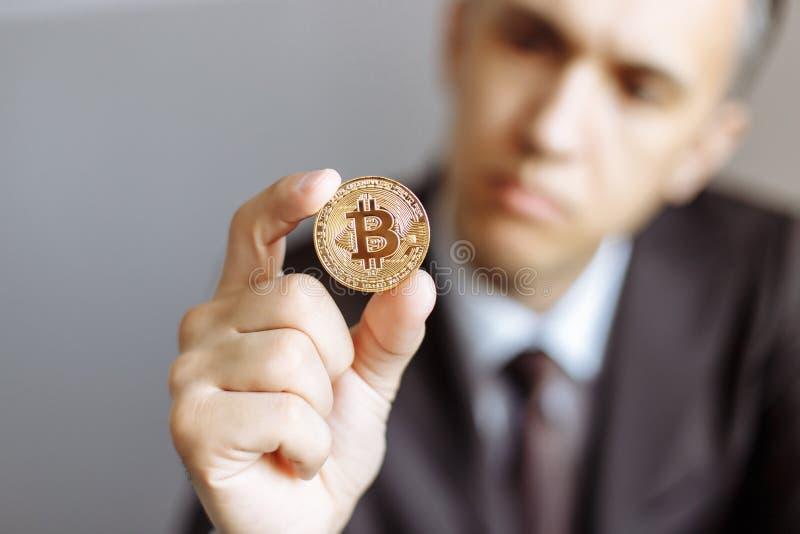 Homem de negócios novo que guarda o símbolo disponivel da moeda cripto do bitcoin - dinheiro virtual eletrônico para a operação b imagens de stock