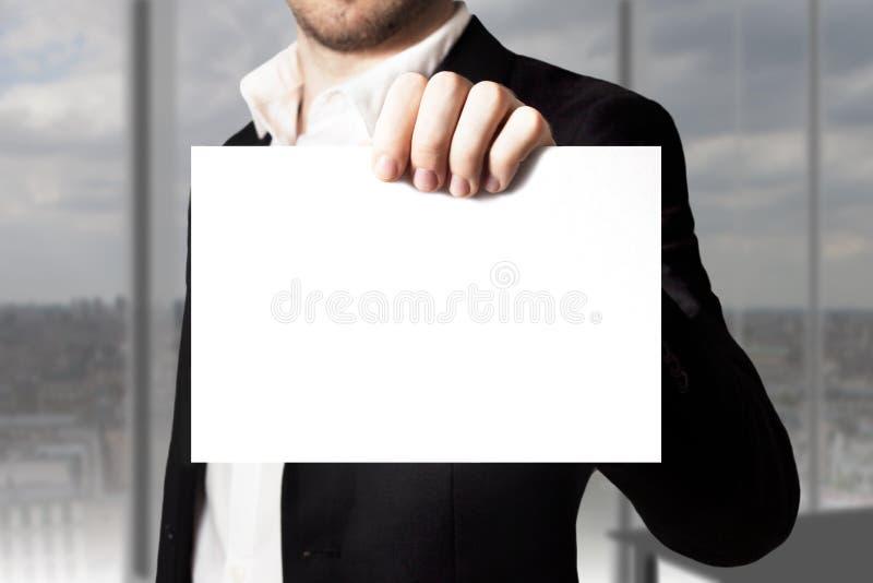 Homem de negócios novo que guarda o sinal vazio branco fotos de stock royalty free