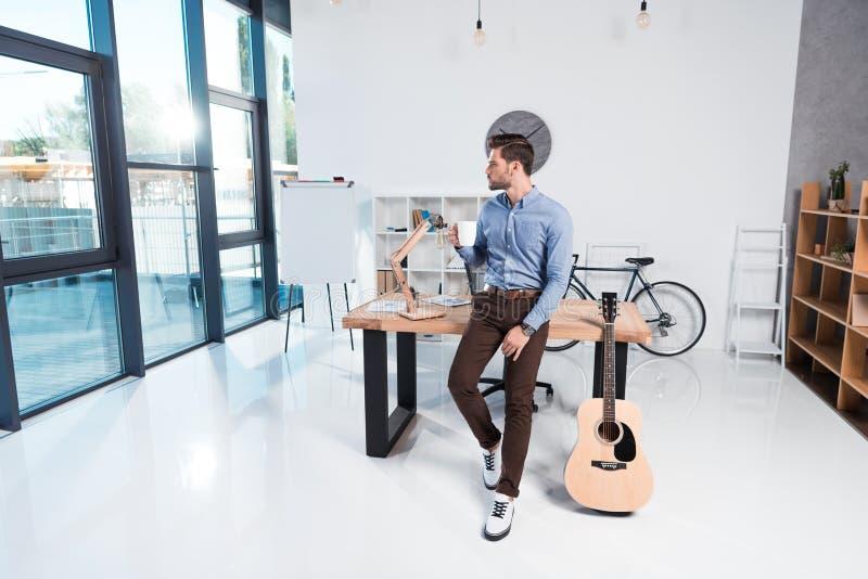 homem de negócios novo que guarda a xícara de café e que olha ausente ao inclinar-se na tabela com guitarra acústica fotos de stock royalty free