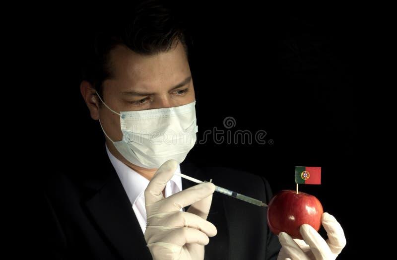 Homem de negócios novo que injeta produtos químicos em uma maçã com Portugu imagem de stock