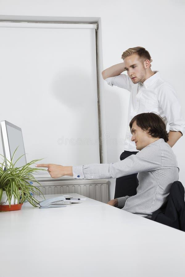 Homem de negócios novo que mostra o ecrã de computador a colega de trabalho confuso na mesa imagens de stock