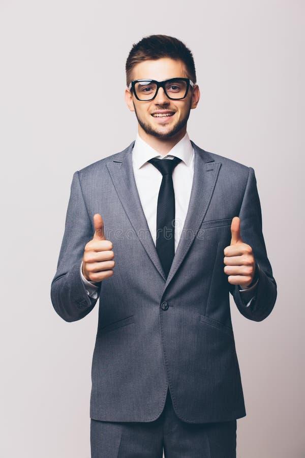 Homem de negócios novo que mostra os polegares acima fotografia de stock