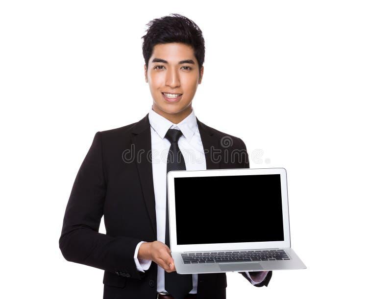 Homem de negócios novo que mostra a tela vazia do laptop fotos de stock