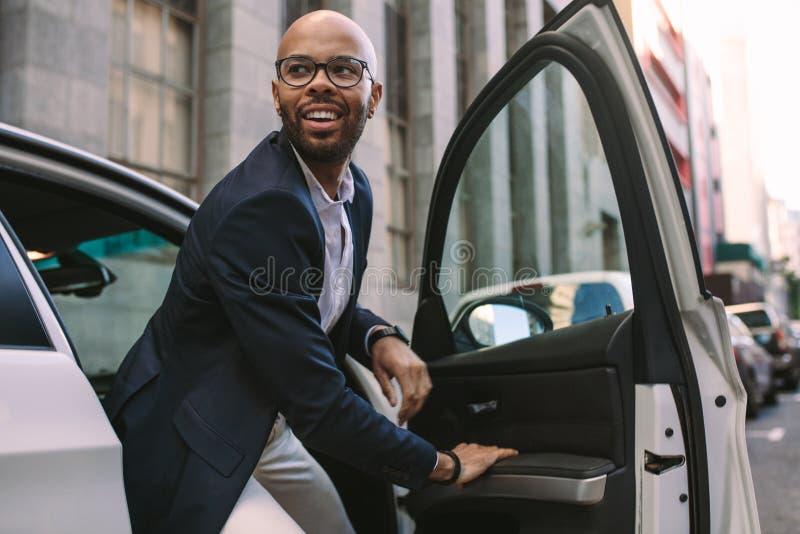 Homem de negócios novo que obtém para baixo do carro fotografia de stock royalty free