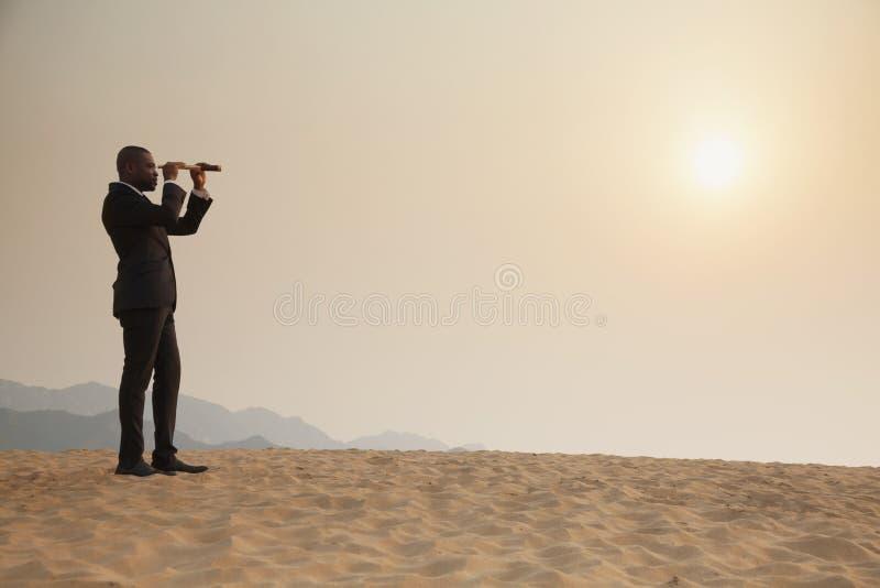 Homem de negócios novo que olha através do telescópio no meio do deserto imagem de stock royalty free