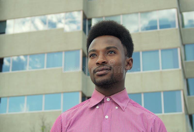 Homem de negócios novo que olha a camisa ausente do rosa do prédio de escritórios imagens de stock royalty free