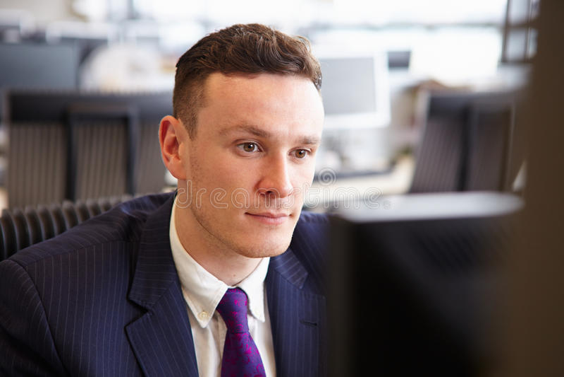 Homem de negócios novo que olha fixamente no tela de computador fotografia de stock royalty free