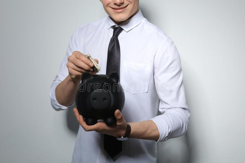 Homem de negócios novo que põe o dinheiro no mealheiro no fundo claro imagem de stock royalty free