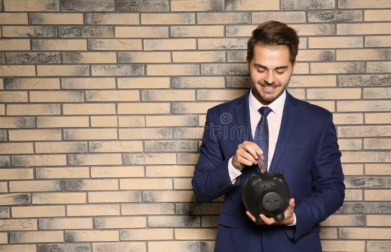Homem de negócios novo que põe o dinheiro no mealheiro perto da parede de tijolo fotografia de stock