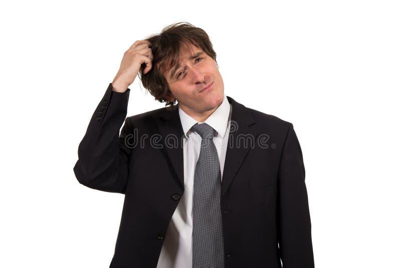 Homem de negócios novo que risca sua cabeça, decisão dura, tiro do estúdio isolado no fundo branco fotografia de stock royalty free