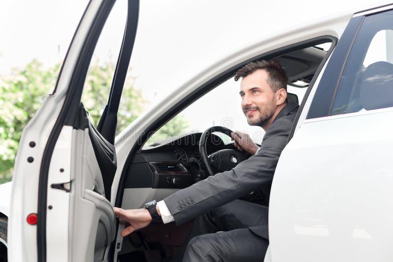 Homem de negócios novo que senta-se em seu carro novo imagens de stock