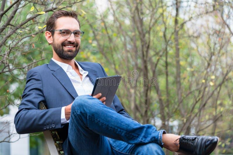 Homem de negócios novo que senta-se no banco que guarda a tabuleta digital imagens de stock royalty free