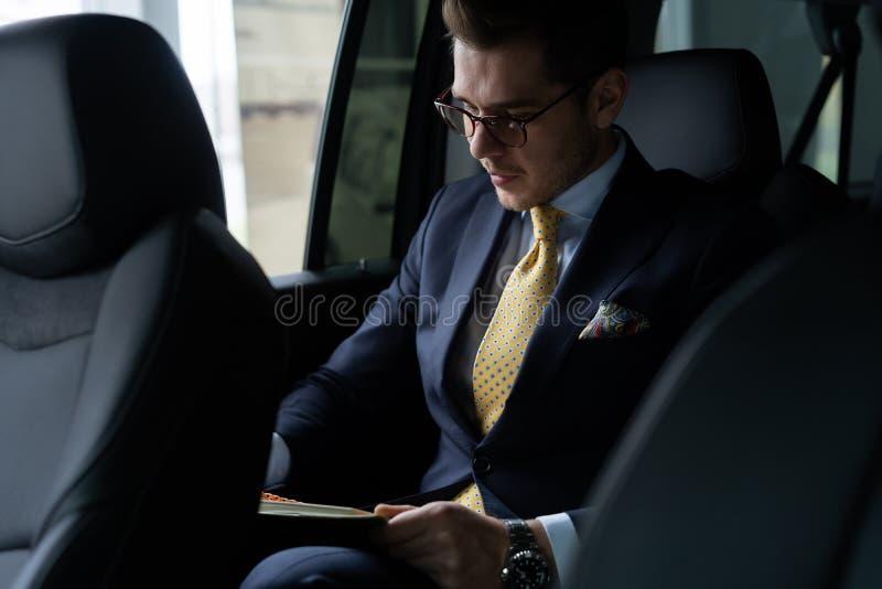 Homem de negócios novo que senta-se no banco traseiro do carro, quando seu motorista conduzir o automóvel fotos de stock