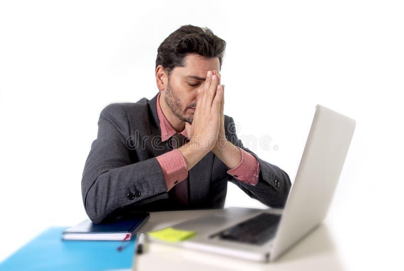 Homem de negócios novo que senta-se no funcionamento de mesa do escritório em desesperado do portátil do computador preocupado no foto de stock