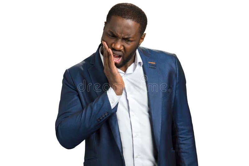 Homem de negócios novo que sofre da dor de dente fotografia de stock