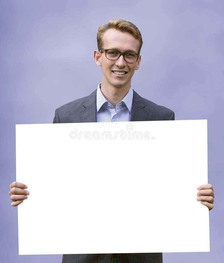 Homem de negócios novo que sustenta um sinal branco imagens de stock