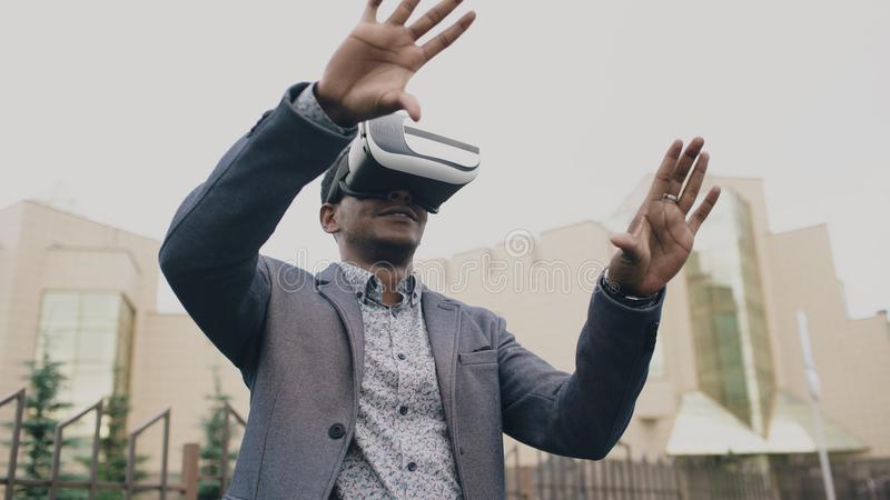 Homem de negócios novo que tem a experiência de VR usando auriculares da realidade 360 virtual fora imagem de stock royalty free