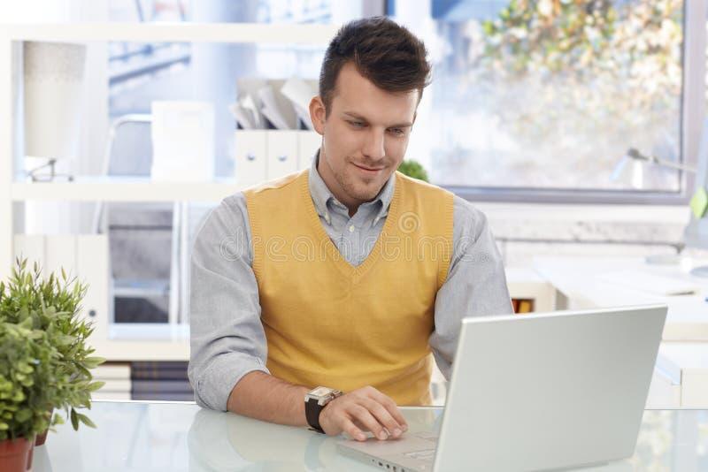 Homem de negócios novo que trabalha com computador portátil foto de stock