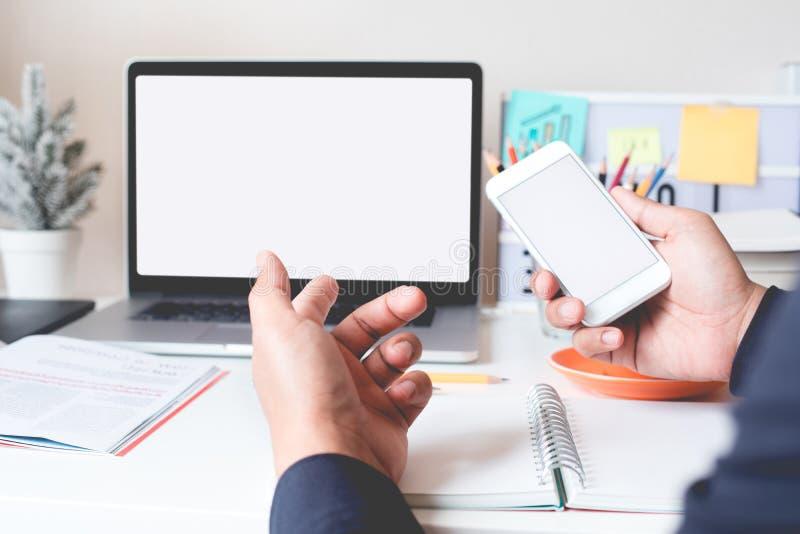 Homem de negócios novo que trabalha com o portátil do smartphone e do computador no worktable Conceitos da conectividade e da vid fotos de stock