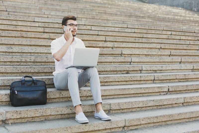 Homem de negócios novo que trabalha com portátil fora imagens de stock royalty free