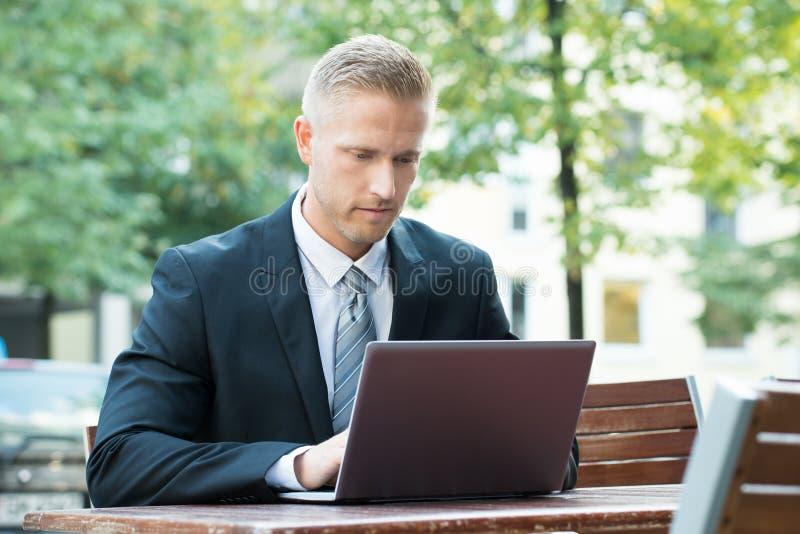 Homem de negócios novo que trabalha no portátil fotos de stock
