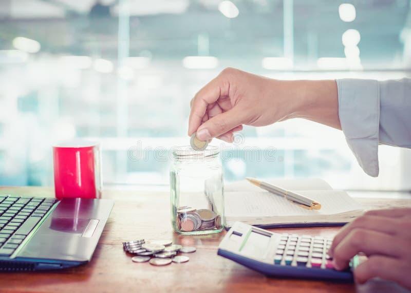 Homem de negócios novo que usa a calculadora para a finança, imposto e salvar o dinheiro fotos de stock royalty free