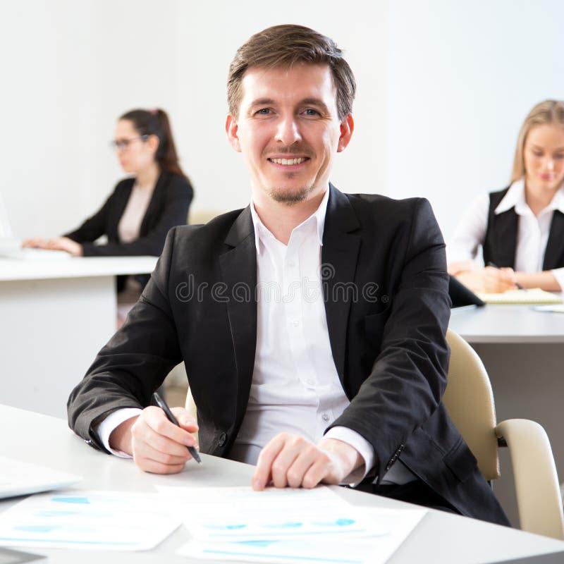 Homem de negócios novo que usa o computador no escritório fotografia de stock