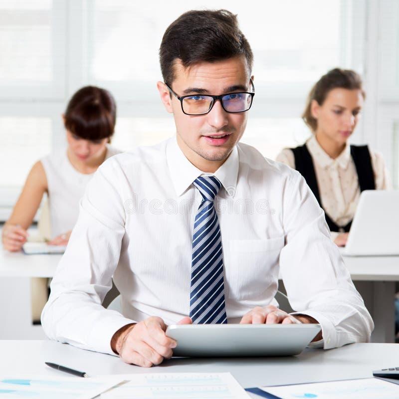 Homem de negócios novo que usa o computador no escritório imagem de stock