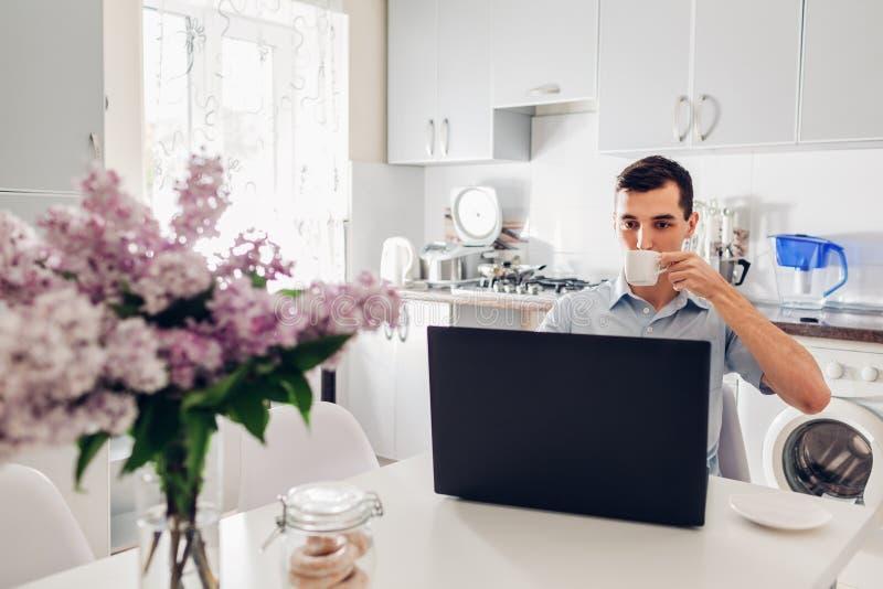 Homem de negócios novo que usa o portátil ao comer o café na cozinha moderna Café da manhã de um empresário fotografia de stock