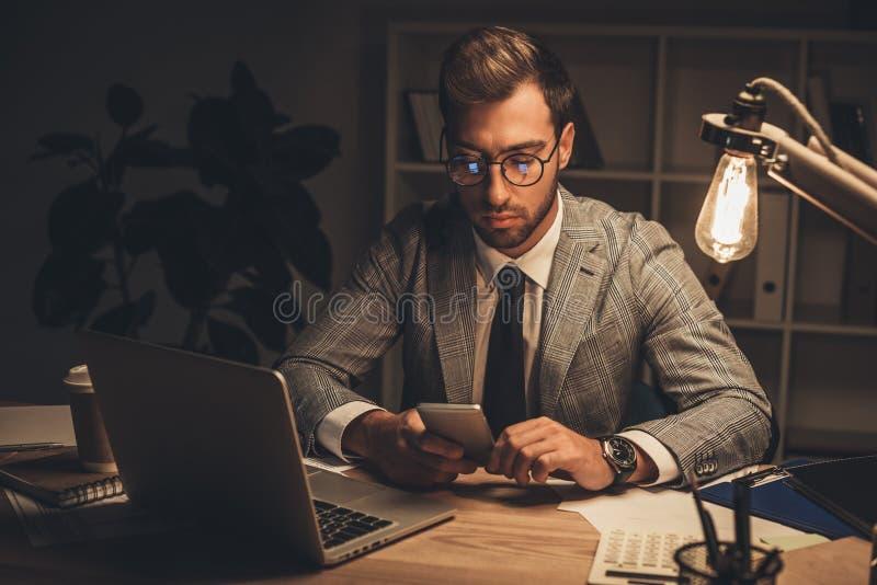homem de negócios novo que usa o smartphone em tarde fotos de stock