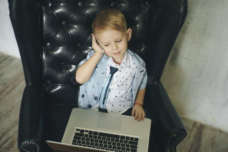 Homem de negócios novo que usa um portátil Criança engraçada nos vidros Forme o retrato do menino considerável pequeno no escritó imagem de stock royalty free