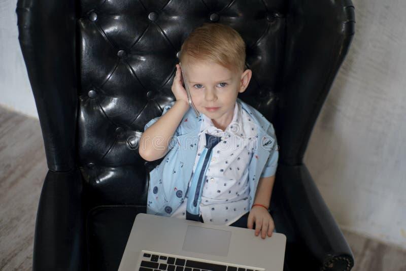 Homem de negócios novo que usa um portátil Criança engraçada nos vidros Forme o retrato do menino considerável pequeno no escritó fotos de stock